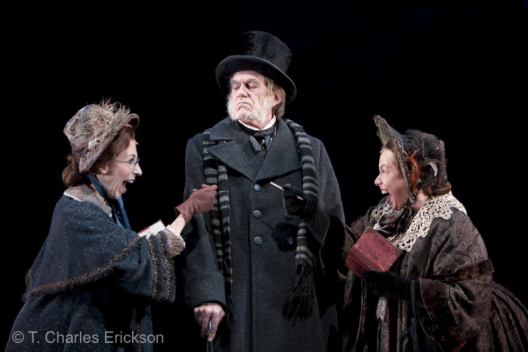 The Solicitors (Piper Goodeve and Michele Tauber) ask Scrooge (Graeme Malcolm) to donate to their cause.