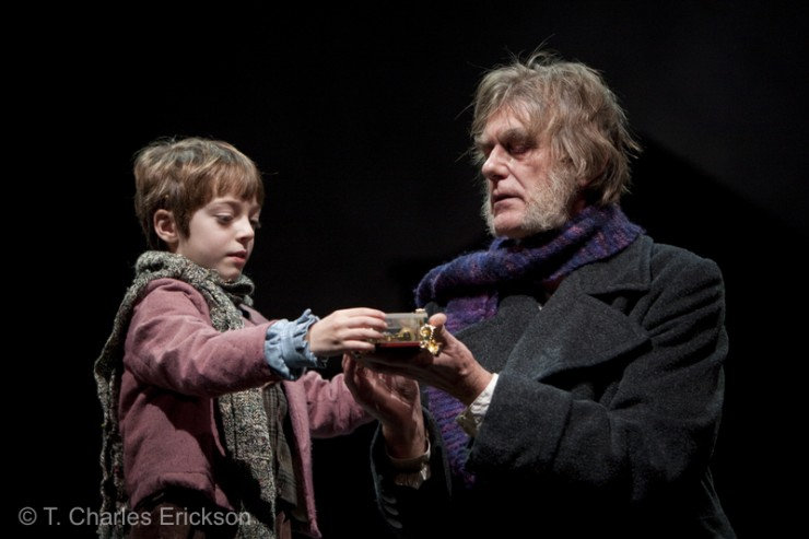 Scrooge (Graeme Malcolm) offers the gift of the music to Tiny Tim (Noah Hinsdale).