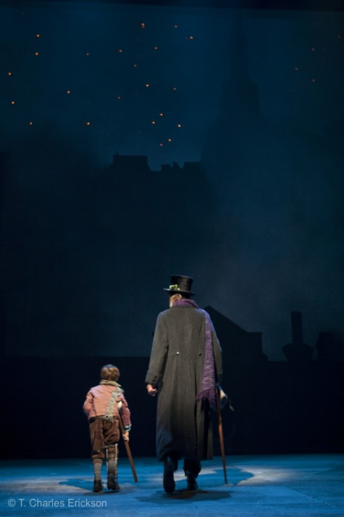 Tiny Tim (Noah Hinsdale) and Scrooge (Graeme Malcolm) walk off together.