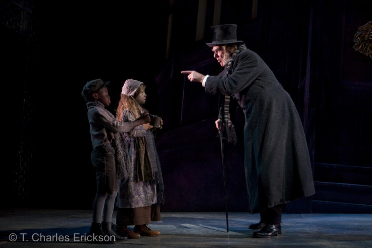 Scrooge (Graeme Malcolm) berates two Beggar Children (Tom Roderiguez and Cara Barkenbush).
