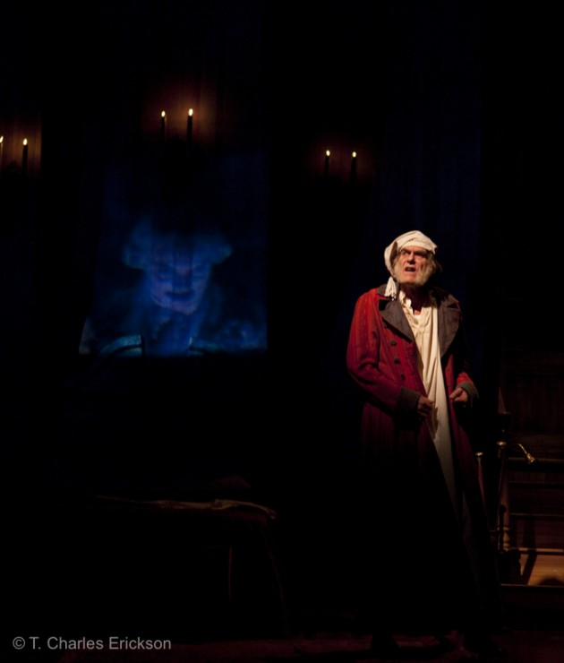 Scrooge (Graeme Malcolm) hears the voice of the spectre of Jacob Marley (Justin Blanchard).