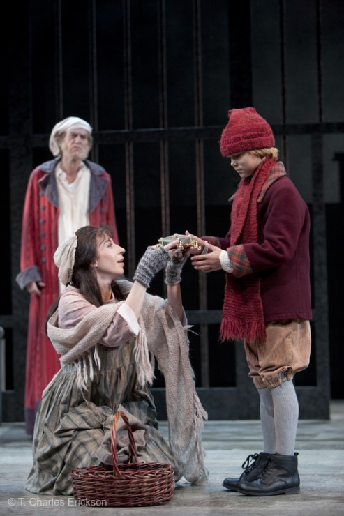 Fan (Piper Goodeve) gives the gift of a music box to Boy Scrooge (Danny Hallowell) while Scrooge (Graeme Malcolm) looks on.