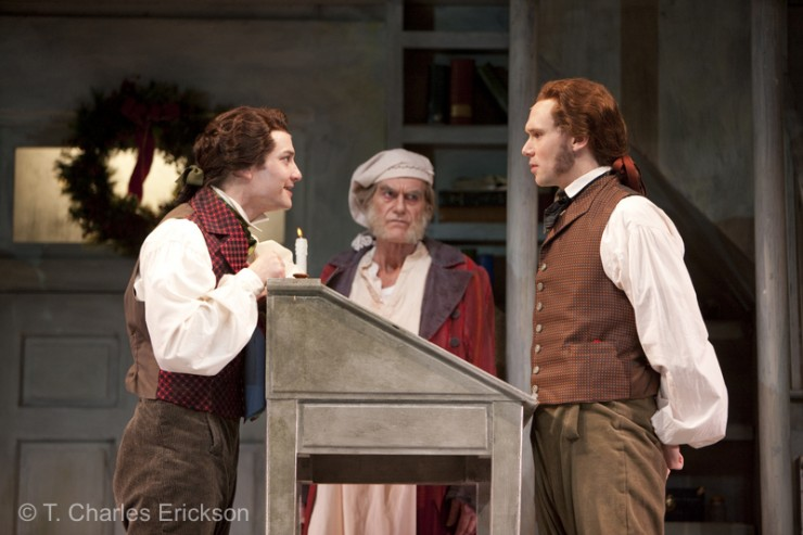 Scrooge (Graeme Malcolm) observes Jacob Marley (Justin Blanchard) speaking with his  younger self (Chris Dunlop).