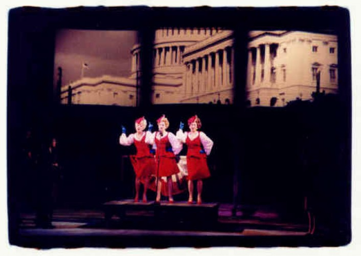 "Ruth is stymied in her efforts to release the refugees from behind yet another fence by the powers that be in Washington as the Mandrake Sisters (Lauren Brody-Stewart, Sierra Rein  and Melissa Lyons) sing ""Buy A Bond Today""."